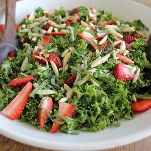 Ensalada de col rizada cruda con aderezo de albahaca vegana, fresas y receta de almendras